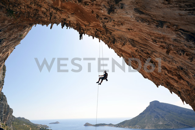 Greece, Kalymnos, climber abseiling in grotto - LMF00676