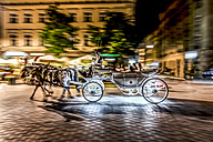 Poland, Krakow, Old Town, Main Square, carriage on the move at night - CSTF01243