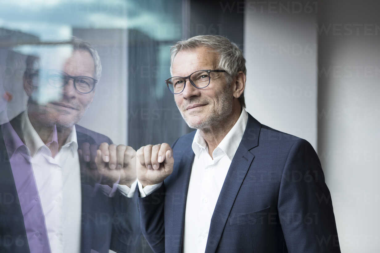 Confident businessman looking out of window - RBF05613 - Rainer Berg/Westend61