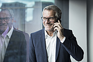 Smiling businessman on cell phone at the window - RBF05616
