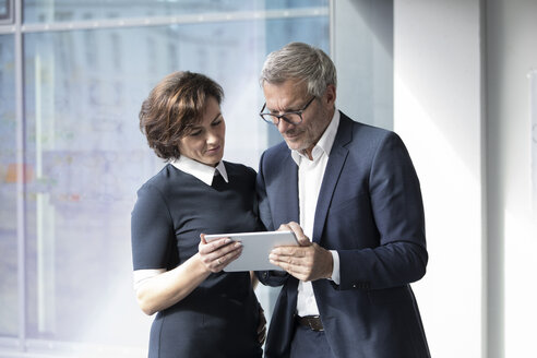Businessman and businesswoman sharing tablet at the window - RBF05622