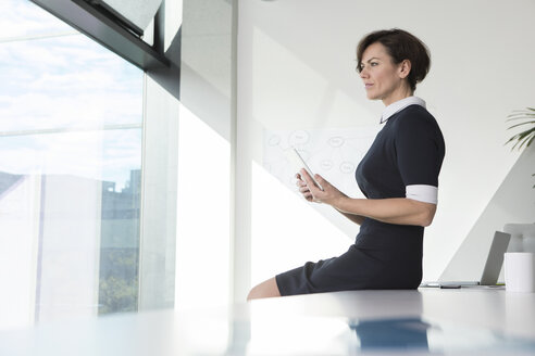 Businesswoman with tablet in office looking out of window - RBF05631