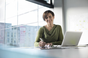 Portrait of smiling businesswoman in office - RBF05634