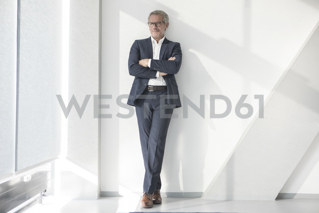 Confident businessman leaning against a wall - RBF05637