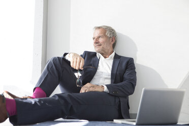 Businessman sitting on the floor next to laptop - RBF05640