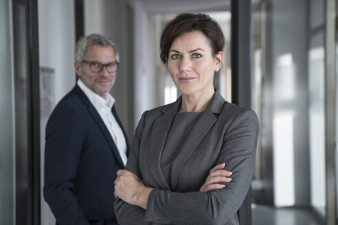 Portrait of confident businesswoman with businessman in background - RBF05655