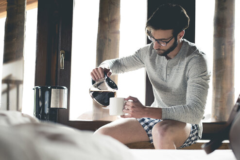 Young man pouring coffee into cup at home - ZOCF00143