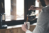 Young man pouring coffee into cup at home - ZOCF00152
