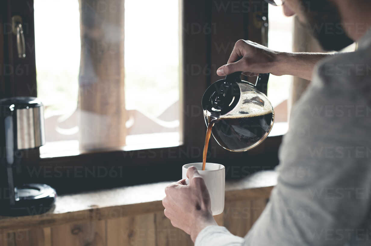 Young man pouring coffee into cup at home - ZOCF00152 - ZoneCreative/Westend61