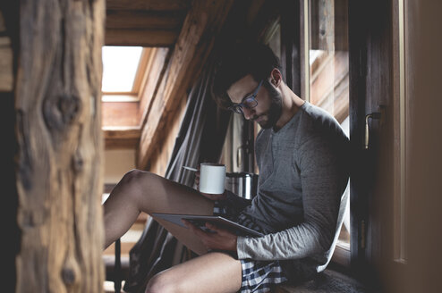 Young man using tablet and drinking coffee at home - ZOCF00158