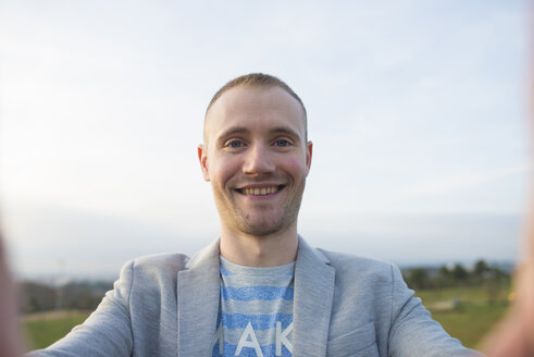 Portrait of smiling man taking selfie - SKCF00265