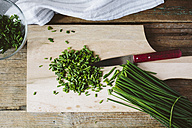 Chopped and whole chives and kitchen knife on wooden board - GIOF01932