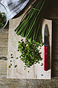 Chopped and whole chives and kitchen knife on wooden board - GIOF01935