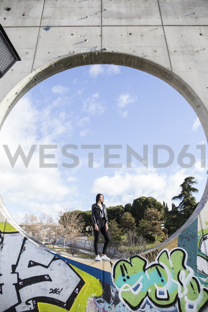 Young woman standing in a circle of a concrete wall - ABZ01932