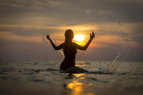Indonesia, Bali, female surfer in the ocean at sunset - KNTF00637