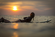 Indonesia, Bali, female surfer in the ocean at sunset - KNTF00640