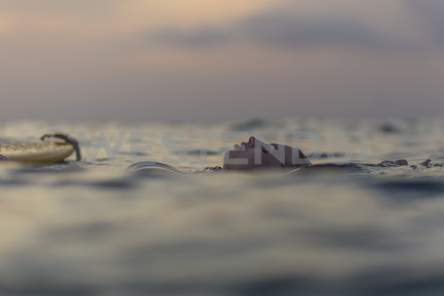 Indonesia, Bali, female surfer in the ocean at sunset - KNTF00643
