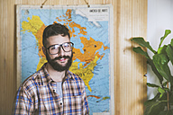 Portrait of bearded man wearing glasses in front of a map - RTBF00681