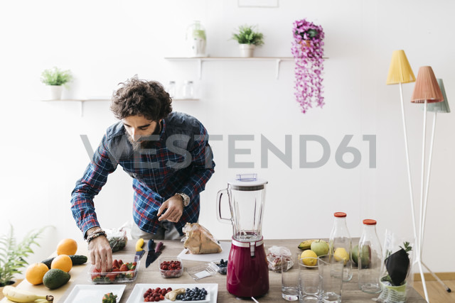 Man preparing smoothies with fresh fruits and vegetables at home - JRFF01204 - Josep Rovirosa/Westend61