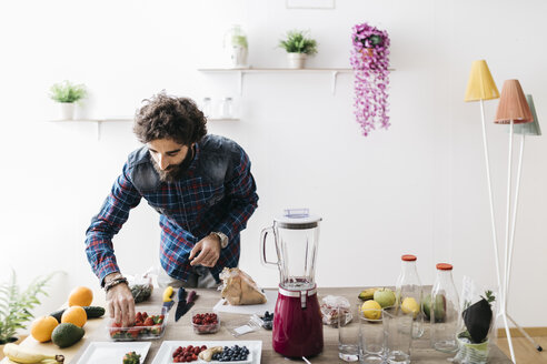 Man preparing smoothies with fresh fruits and vegetables at home - JRFF01204