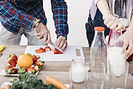 Couple preparing smoothies with fresh fruits and vegetables, partial view - JRFF01207