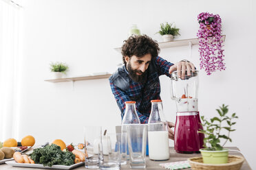 Man preparing smoothies with fresh fruits and vegetables at home - JRFF01216