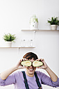 Smiling woman covering her eyes with halves of avocado - JRFF01231