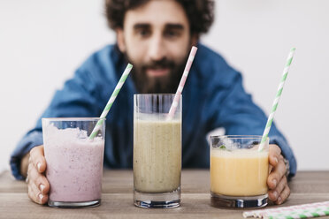 Man showing three glasses of various smoothies - JRFF01243