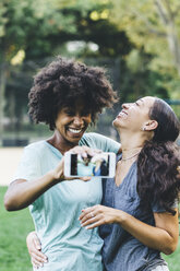 Two happy best friends taking selfie with smartphone in a park - GIOF01986