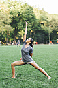 Young woman doing yoga exercise in a park - GIOF01989