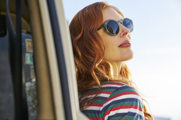 Young woman wearing sunglasses leaning against car - FMKF03487