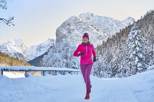 Austria, Tyrol, Karwendel, Riss Valley, woman jogging in winter - MRF01699