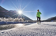 Germany, Bavaria, Isar valley, Vorderriss, woman jogging in winter - MRF01702