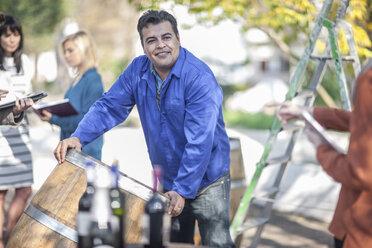 Wine barrel worker with saleswoman outdoors - ZEF12881
