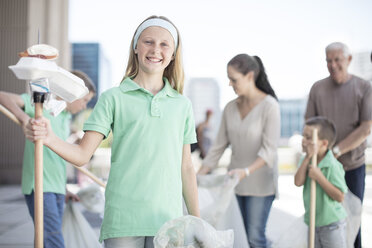 Group of volunteering children collecting garbage with litter sticks - ZEF12890