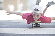 Boy skateboarding in the street, lying on belly - ZEF12899