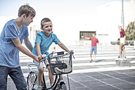 Boy teaching little brother how to ride a bycicle - ZEF12908