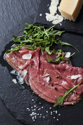 Beef Carpaccio with rocket, olive oil, parmesan, pepper and salt on slate - CSF27905