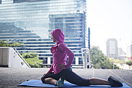 Young woman stretching on gymnastics mat in the city - ZEF12934