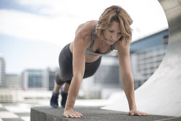 Young woman doing push-ups in the city - ZEF12937