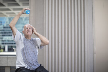 Senior athlete taking a break pouring water over his head - ZEF12949
