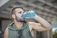 Athlete taking a break in the city drinking water from bottle - ZEF12952