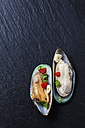 Green mussels with tomatoes, capsicum and garlic, on black slate slab - CSF27948