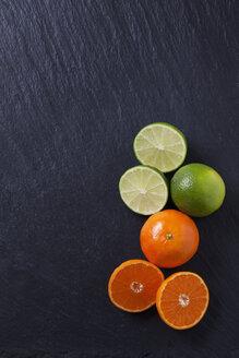 Limes and tangerines on black slate slab - CSF27960