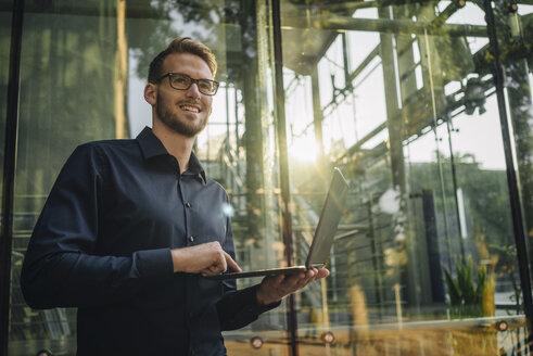 Smiling businessman using laptop in lobby - KNSF01050