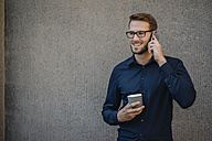 Smiling businessman talking on cell phone - KNSF01065