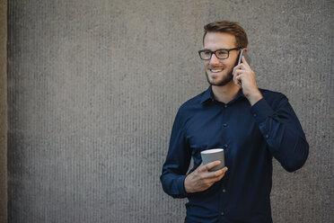 Smiling businessman talking on cell phone - KNSF01065