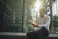 Businessman reading book in lobby - KNSF01071