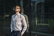 Businessman leaning against glass wall - KNSF01074