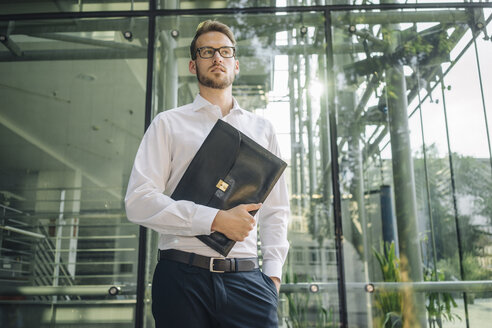 Businessman holding briefcase in lobby - KNSF01077